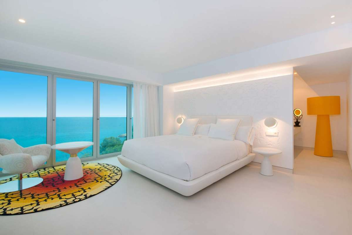View on the bed, a lounge suite and the glassed wall to the terrace, opening the sight towards the sea