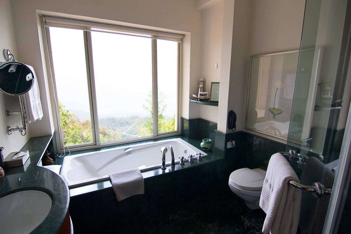 View on the bath tub in front of a big glass front at one of the bathrooms at Ananda hotel
