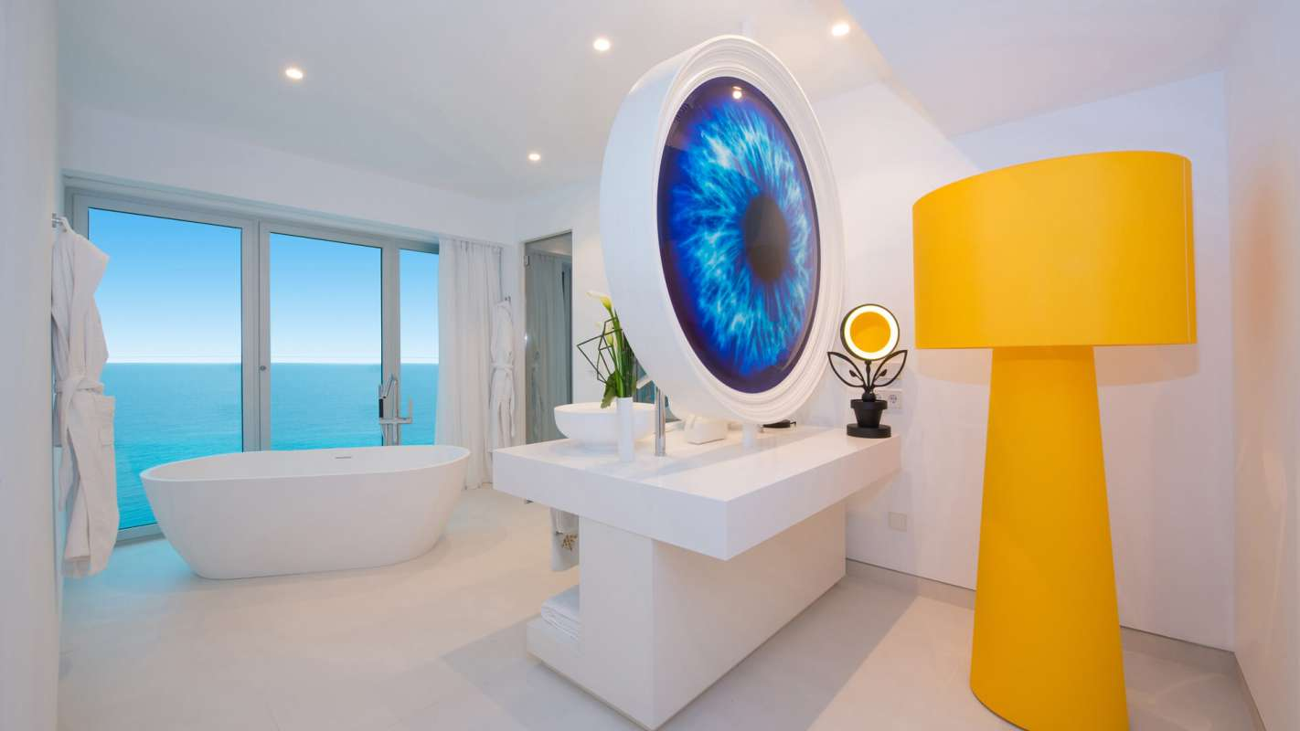 View on the modern furniture of a bathroom, including a freestanding tub with sea view